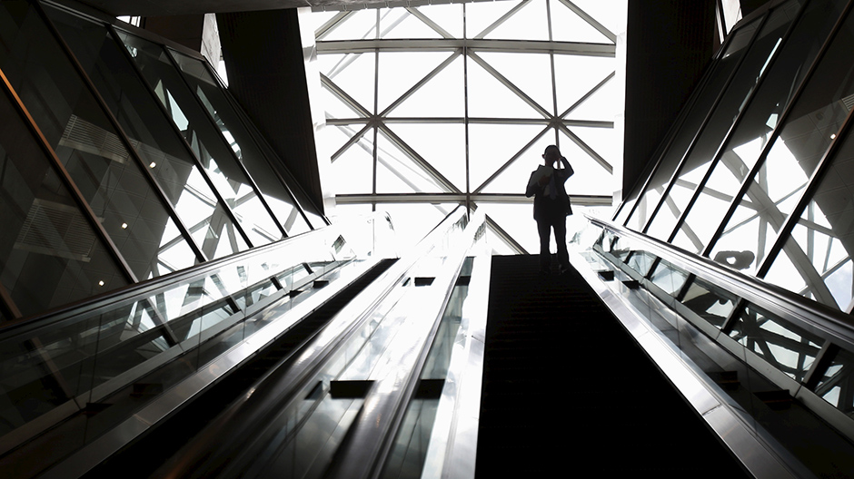 A man scratching his head rides on an escalator at a business district in Tokyo, Japan, May 25, 2015.