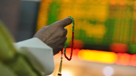 An investor holds the tasbeeh as he monitors electronic boards displaying stock information