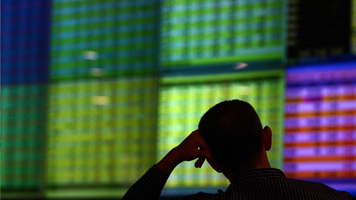 A dealer monitors price movements on an electronic board at the investors gallery in the Amman Stock Exchange