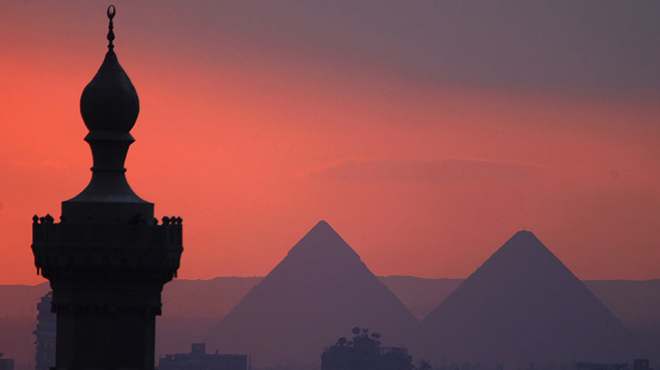 The sun sets on the minarets and the Great Pyramids of Giza