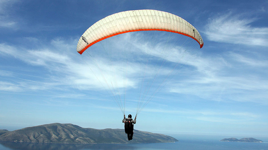 A paraglider flies over the city of Vlore during an annual Balkan competition, some 150 km (94 miles) from the capital Tirana, May 9, 2009.